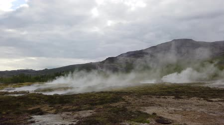 гейзер : Strokkur geothermal landscape in Iceland with hot water and smoke, Strokkur, Iceland. High concentration of volcanoes is often an advantage in the generation of geothermal energy in Iceland Стоковые видеозаписи