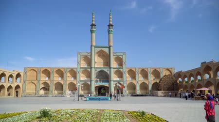 yazd : Yazd, Iran - May 2019: Jameh Mosque entrance gate with minarets with iranian people and tourists walking around Stock Footage