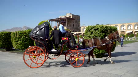 Isfahan, Iran - May 2019: Tourists having a horse carriage ride around Isfahan Naqsh-e Jahan Square also called Imam Square Stock Footage