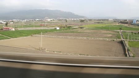 headstock : Taiwanese Rural Scene Out of The Window of a Driving High Speed Train in the Daytime.