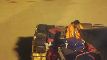 jiangsu : Nanjing Jiangsu China February 11 2015: A Ground Staff is Unloading the Cargo From the Airplane, His Movement is Very Violent. This Kind of Violence Unloading Causes Passengers Bag Broken.