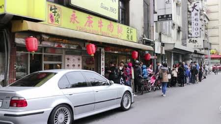 kuyruk : Taipei Taiwan ROC February 09 2015: People Quening up in Front of the Gate of the Yongkang Beef Noodles Restaurant the Most Famous Noodle Restaurant in Taipei Because of Its Delicous Beef Noodle. Stok Video