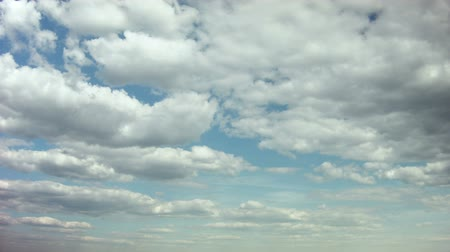 Beautiful white clouds soar across the screen in time lapse fashion over a deep blue background