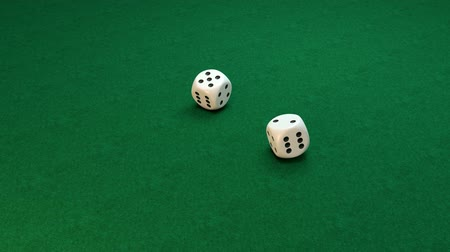 Slow motion of rolling white dice on green background, number 4-1 Stock mozgókép