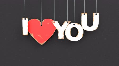 cherish : Beautiful 3D animation of heart with text I love you. Hanging on the ropes cardboard text falls from top to bottom on an black background Stock Footage