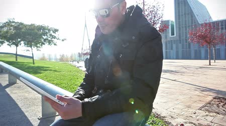 Mobile devices lifestyle.Internet concept.Sunbeam and sunset.Man sitting in the street using tablet.Lifestyle and modern life cityscape.Technology and communication concept