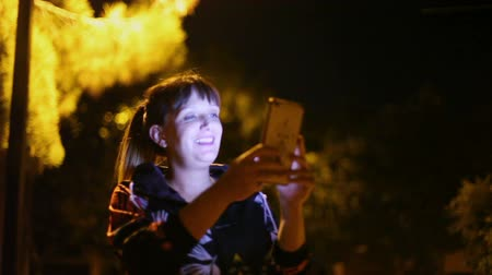 Lifestyle and technology. Young woman smiling with sportswear and her smartphone in her hand, walking through the city at night, with streetlights.