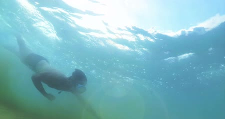 Diving and swimming in ocean. Underwater sport.Young man having fun diving in the sea. Adventures and entertainment on the beach with holiday activities under sunset Stock Footage