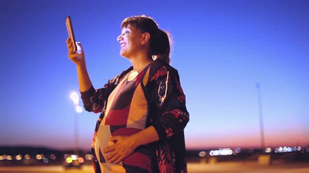 Lifestyle and technology. Pregnant young woman smiling with sportswear and her smartphone in her hand, walking through the city at night, with streetlights. Stock Footage