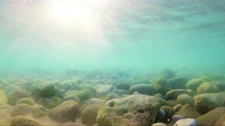 Sea and ocean background. Slow and beautiful underwater scene with air bubbles,stones and beach sand floating up and sun shining through the water