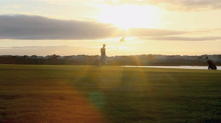 поле для гольфа : Golfer silhouette playing at twilight in Algarve famous golf destination, Portugal. Стоковые видеозаписи