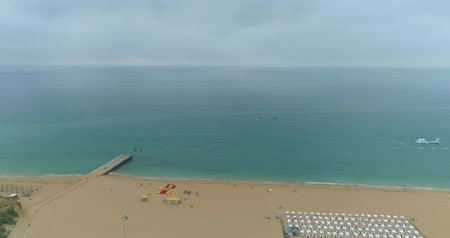 halászok : Aerial view of Praia dos Pescadores (Fishermen beach) in a cloudy day, famous destination in Albufeira, Algarve, Portugal. Stock mozgókép