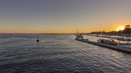 dockyard : Sunset pan timelapse seascape view of Olhao Marina, waterfront to Ria Formosa natural park. Algarve. Portugal.