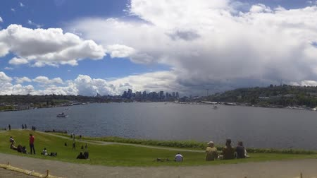 SEATTLE - 10 DE JUNIO DE 2018 - Timelapse Lake Union boats, personas en Gasworks Park un domingo por la tarde. Horizonte de Seattle con nubes de tormenta moviéndose en Archivo de Video