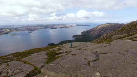 Woman is hiking on the top of a mountain in Norway, aerial view