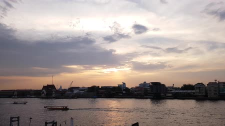 phraya : Bangkok city skyline,  Timelapse, Beautiful sunset over Chao Phraya River skyline, Sunset sky background, Long tail boat running on the Chao Phraya River, River view in Thailand.