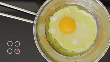 frigideira : Overhead view of a fresh egg frying in a stainless steel pan on the hob. Slow zoom in with clockwise twist.