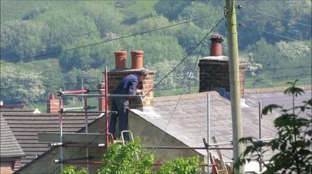 dach : WREXHAM, UK - May 25, 2017: Roofer repairing flashing on chimney stack on a slate roof of a domestic house. Standing on scaffolding. High angle point of view. Countryside background. Hand held.