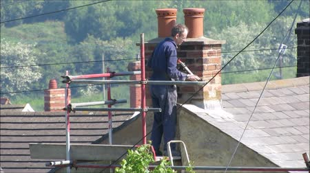 dach : WREXHAM, UK - May 25, 2017: Roofer repairing flashing on chimney stack on a slate roof of a domestic house. Standing on scaffolding. Close up, high angle point of view. Countryside background. Hand held.