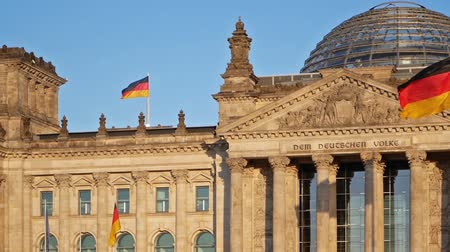 chancellor : German Flags Fluttering In The Wind At The Reichstag Building In Berlin, Germany, Fast Panning Shot