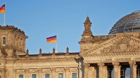 bundestag : German Flags Fluttering In The Wind At The Reichstag Building In Berlin, Germany, Slow Panning Shot Stock Footage