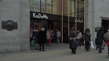 немецкий : BERLIN, GERMANY - FEBRUARY 8, 2019: Buyers At The Entrance of Kadewe Department Store At Wittenbergplatz In Berlin, Germany Стоковые видеозаписи