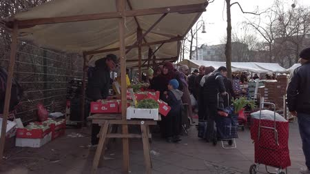retailer : BERLIN, GERMANY - FEBRUARY 6, 2019: Merchants And Buyers At A Turkish Food Market Square In Berlin, Germany Stock Footage