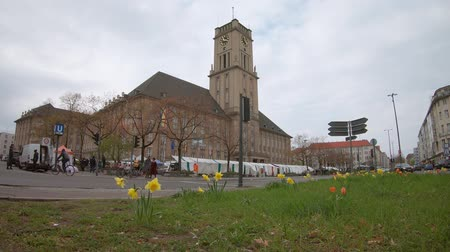 városháza : BERLIN, GERMANY - APRIL 13, 2019: Traffic And Market At Rathaus Schoneberg, City Hall For The Borough of Tempelhof-Schoneberg In Berlin, Germany Stock mozgókép