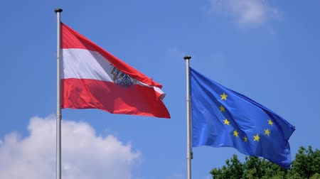 austríaco : Austria And EU Flag Fluttering Against A Blue Cloudy Sky