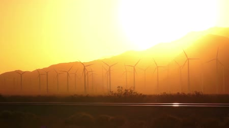 gerador : Dramatic color at sunset washes wind turbines in orange color Vídeos