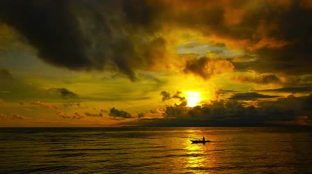 pólos : A golden sunrise video facing the ocean from Dumaguete City shores, Negros Oriental, Philippines. Mellow breeze moves the sun painted cumulus clouds over peaceful waves, while the sun is just over the horizon. Silhouette of a local fisherman can be seen p