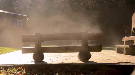 smutek : Tranquil autumn backyard bench with evaporating dew in the morning