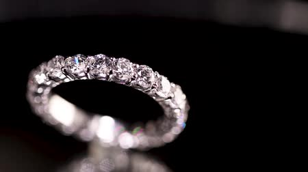 proposta : Engagement diamond ring rotating on black background, macro with shallow DoF
