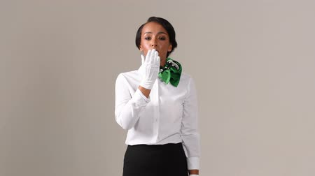 air kiss : Flight attendant sending air kiss. Black beautiful woman wearing stewardess uniform and white gloves on gray background. Stock Footage