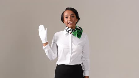 attendant : Flight attendant is greeting. Black beautiful woman wearing stewardess uniform and white gloves on gray background. Stock Footage