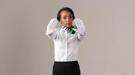 aircraft cabin : Flight attendant showing stop gesture. Black beautiful woman wearing stewardess uniform and white gloves on gray background.