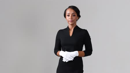 attendant : Flight attendant active listening. Black beautiful woman wearing stewardess black dress and white gloves on gray background.