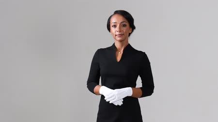 attendant : Flight attendant. Black beautiful woman wearing stewardess black dress and white gloves on gray background.