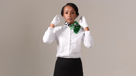 servant : Flight attendant showing emergency exits. Black beautiful woman wearing stewardess uniform and white gloves on gray background. Stock Footage