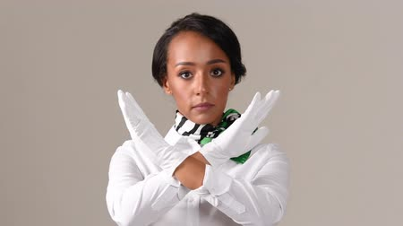 bastante : Flight attendant showing stop gesture. Black beautiful woman wearing stewardess uniform and white gloves on gray background.