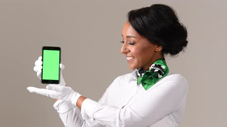 attendant : Flight attendant showing smartphone with green screen. Black beautiful woman wearing stewardess uniform and white gloves on gray background.