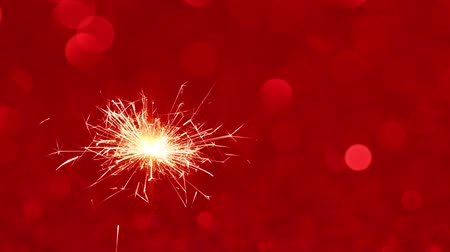 освещенный : Sparkler burning against Red Christmas or New Year festive background