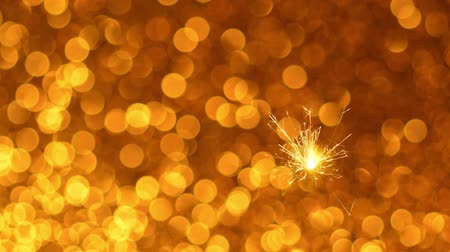 освещенный : Sparkler burning against Golden Christmas or New Year festive background