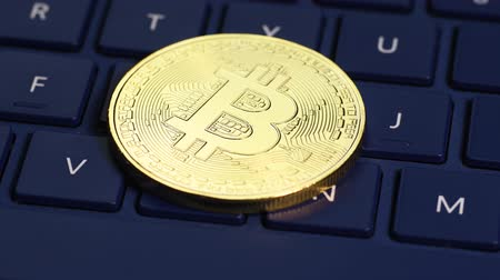 monety : Bitcoin cryptocurrency rotating seamless loop. Golden coin on laptop keyboard, macro shot.