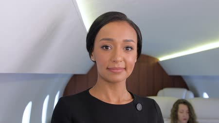 milliomos : Stewardess portrait in private jet. Female biracial flight attendant smiling inside of business airplane cabin with passengers on background.