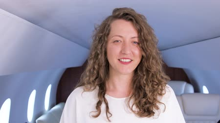 attendant : Businesswoman portrait in private jet. Well dressed, confident female caucasian entrepreneur smiling inside of business airplane cabin.