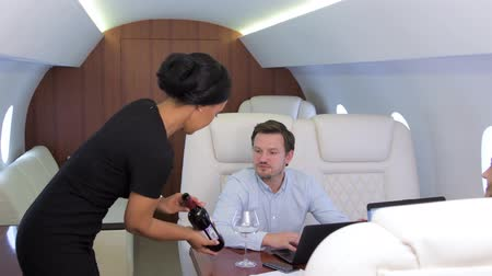Work on laptop on board of private jet. Biracial flight attendant offering and pouring glass of wine for caucasian businessman and businesswoman travel inside of business airplane cabin.