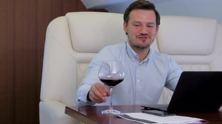 Work on laptop on board of private jet. Businessman comfortably discussing with partner while drinking wine inside of business airplane cabin.