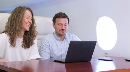 first class : Making video call on laptop on board of private jet. Two caucasian businessman and businesswoman working while travelling inside of business airplane cabin.