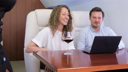 Making video call on laptop on board of private jet. Biracial flight attendant offering glass of wine for caucasian businessman and businesswoman travel inside of business airplane cabin. Stock mozgókép